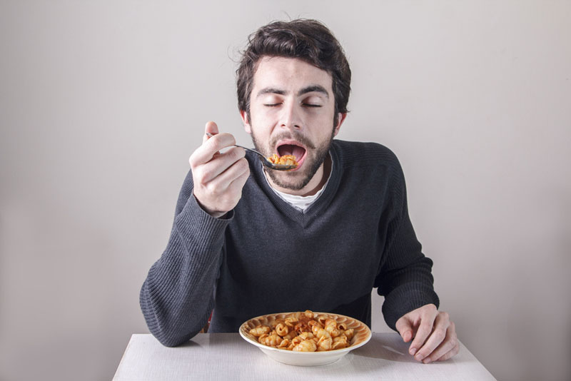 Man eating pasta ravenously